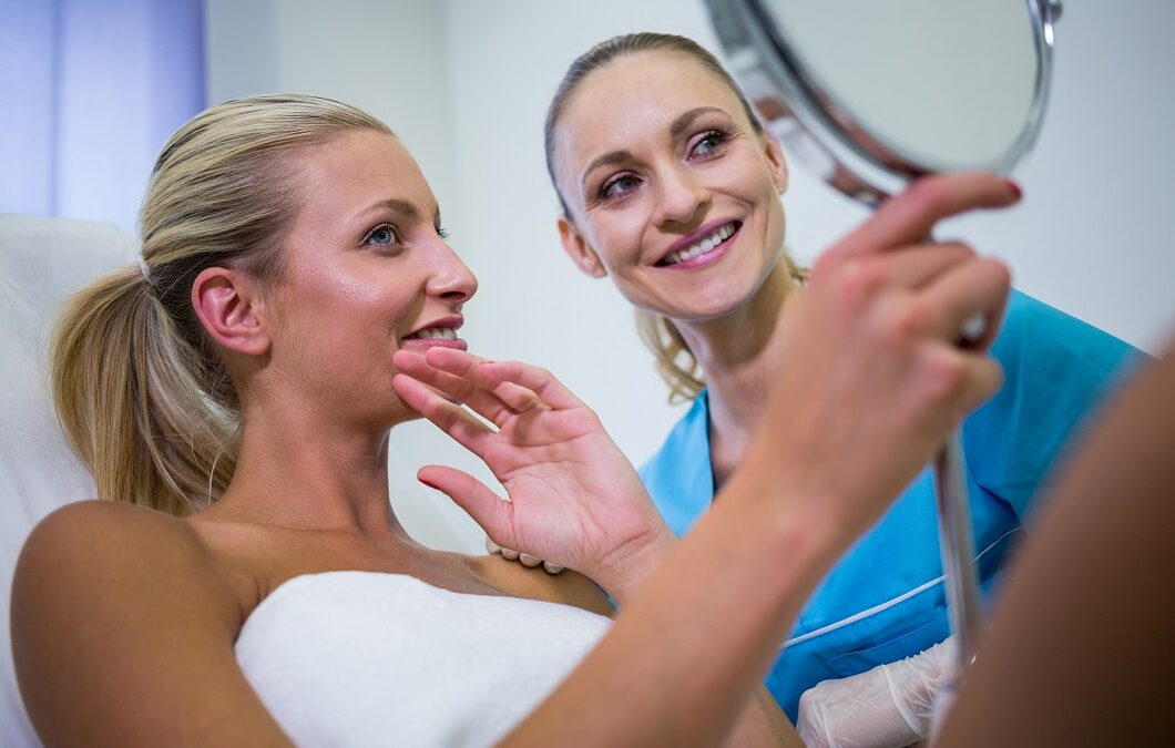 Happy woman checking her skin in the mirror after receiving cosmetic treatment